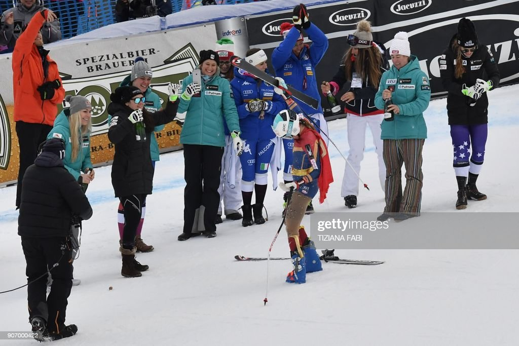 Julia Mancuso (C) of the USA wearing a 'Wonder Woman' ski suit celebrates her last competition with teammates after crossing the finish line of the FIS Alpine World Cup Women's Downhill replacing Val d'Isere event on January 19, 2018 in Cortina d'Ampezzo, Italian Alps. Four-time Olympic medallist Julia Mancuso has announced she will retire from alpine skiing after a farewell run in the women's World Cup downhill in Cortina d'Ampezzo. (L) Lindsey Vonn The 33-year-old American has battled a degenerative hip problem and failed to qualify for a fifth Winter Olympics in South Korea next month. PHOTO / Tiziana FABI