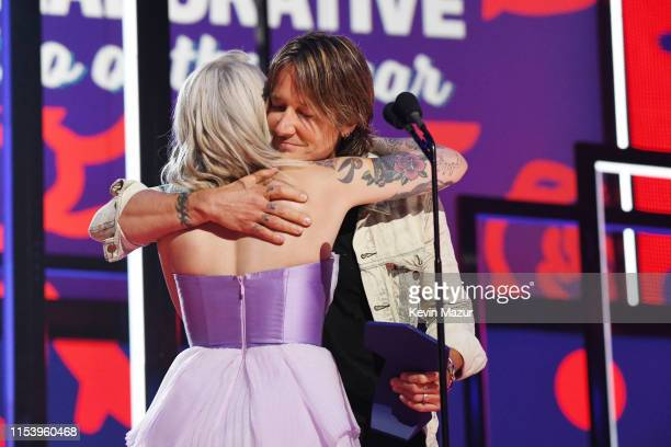Julia Michaels and Keith Urban accept an award at the 2019 CMT Music Awards at Bridgestone Arena on June 05 2019 in Nashville Tennessee
