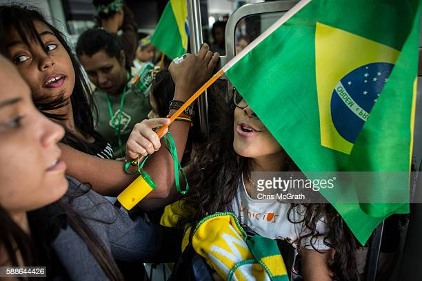 Julia Muniz from the Cantagalo 'favela' community plays around with a Brazilian flag on the subway while travelling to the Olympic Rugby 7's on...