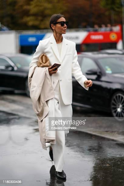 Julia Pelipas wears a white blazer jacket, a beige bag, pants, sunglasses, holds a trench coat, black shoes, outside Chanel, during Paris Fashion...