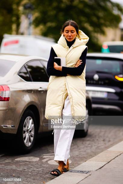 Julia Pelipas wears a white sleeveless puffer coat white pants outside Chanel during Paris Fashion Week Womenswear Spring/Summer 2019 on October 2...