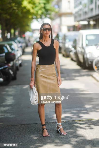 Julia Pelipas wears sunglasses a black top a shiny light camel leather skirt a large white clutch different colors gladiator sandals white and black...