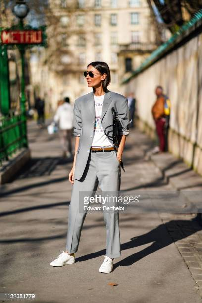 Julia Pelipas wears sunglasses a gray blazer jacket a tshirt a brown leather belt gray suit pants white shoes outside Dior during Paris Fashion Week...