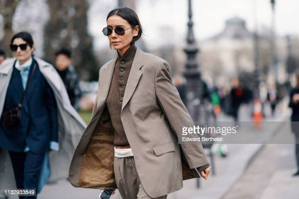 Julia Pelipas wears sunglasses a gray blazer jacket a white belt gray pants a polo shirt outside Paco Rabanne during Paris Fashion Week Womenswear...