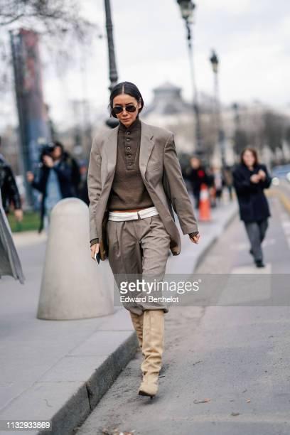 Julia Pelipas wears sunglasses a gray blazer jacket a white belt gray pants beige boots a polo shirt outside Paco Rabanne during Paris Fashion Week...