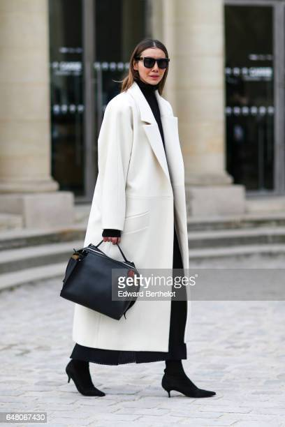 Julia Pelipas wears sunglasses a white coat a black leather bag and black heels and attends the Christian Dior show as part of the Paris Fashion Week...