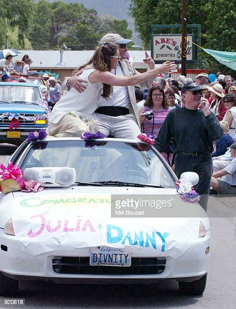 Julia Roberts and Daniel Moder impersonators wave to onlookers as a banner congratulating Roberts and Moder on their wedding day is on display during...