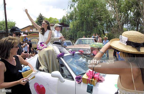 Julia Roberts and Daniel Moder impersonators wave to onlookers during the Fourth of July parade on July 4 2002 in Arroyo Seco New Mexico Roberts...