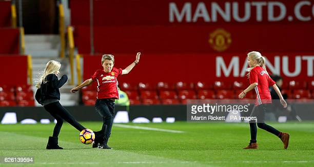 Julia Roberts' children Patricia, Phinnaeus and Henry play football on the pitch after the Premier League match at Old Trafford, London.
