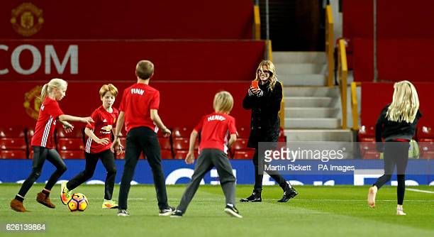 Julia Roberts takes photographs as her children Patricia, Phinnaeus and Henry play football on the pitch after the Premier League match at Old...