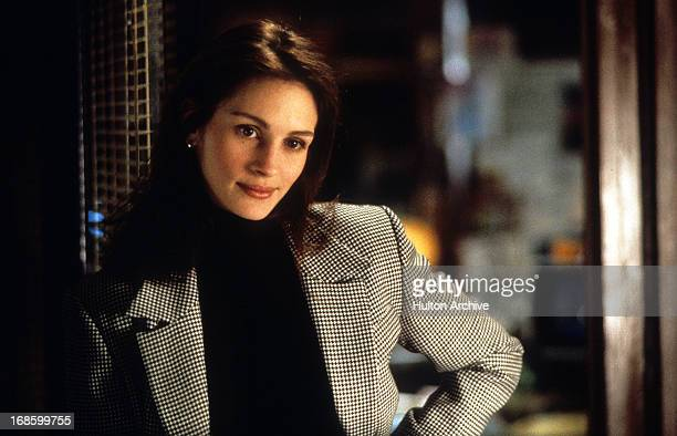 Julia Roberts wearing a hounds tooth jacket as she stands with her hand on her hip in a scene from the film 'I Love Trouble' 1994