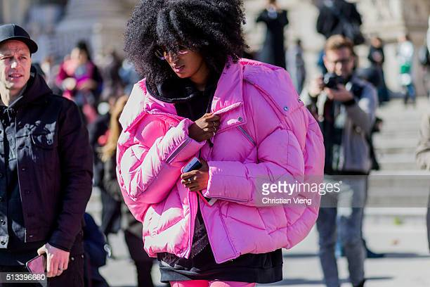 Julia Sarr Jamois wearing a huge pink feather down jacket and a black hoody outside Maison Margiela during the Paris Fashion Week Womenswear...