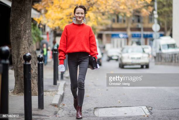 Julia wearing earrings red knit white button shirt with long sleeves skinny denim jeans leather shoes clutch is seen during Tbilisi Fashion Week...