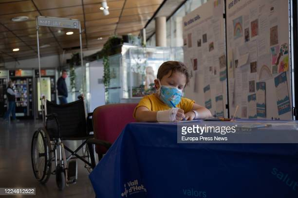 Julian a boy admitted to the Children's Unit of the Vall d'Hebrón Hospital for a rare disease and pending lung transplantation paints a drawing for a...