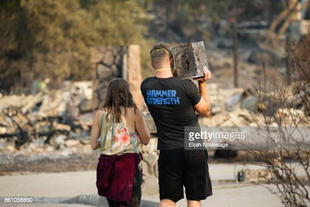 Julian and Lisa Corwin carry a neighbor's safe back to the remains of their home in the Fountaingrove neighborhood on October 13 2017 in Santa Rosa...