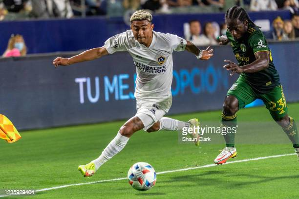 Julian Araujo of Los Angeles Galaxy battles Yimmi Chara of Portland Timbers during the game at the Dignity Health Sports Park on October 16, 2021 in...