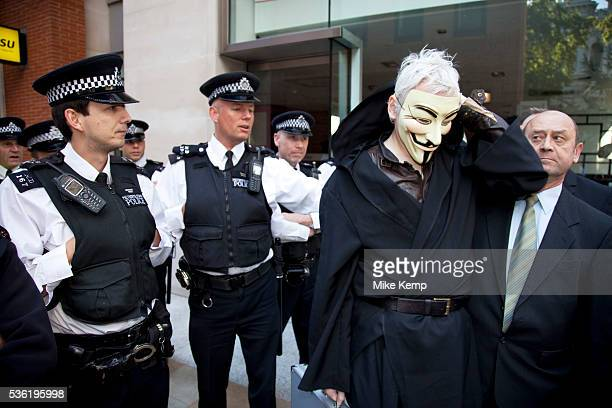 Julian Assange at the Occupy London demonstration 15th October 2011. Seen here after arriving in a taxi with his own security, he tries to get...