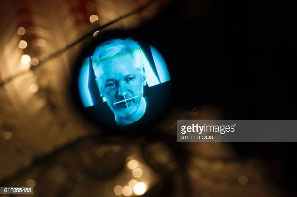 Julian Assange, founder of the online leaking platform WikiLeaks, is seen through the eyepeace of a camera as he is displayed on a screen via a live...