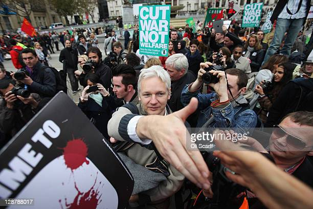 Julian Assange founder of the WikiLeaks website shakes the hand of a supporter as he leaves Trafalgar Square after addressing the crowd during the...