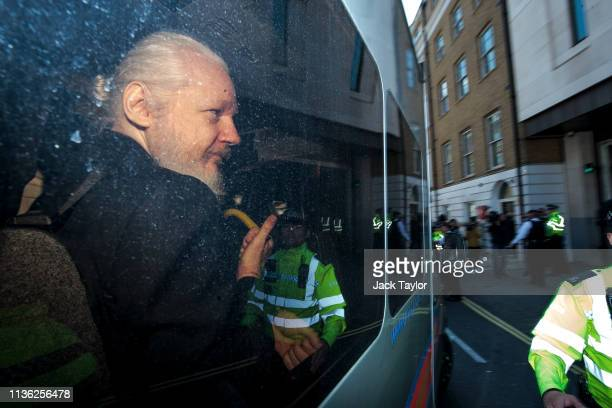 Julian Assange gestures to the media from a police vehicle on his arrival at Westminster Magistrates court on April 11 2019 in London England After...