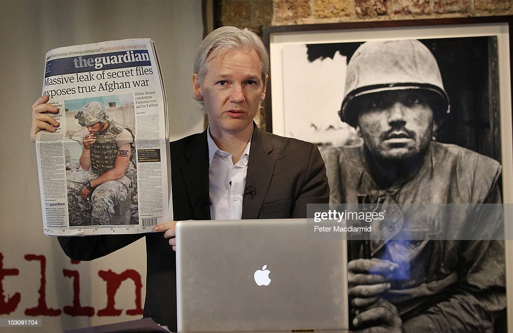 Julian Assange of the WikiLeaks website holds up a copy of The Guardian newspaper as he speaks to reporters in front of a Don McCullin Vietnam war photograph at The Front Line Club on July 26, 2010 in London, England. The WikiLeaks website has published 90,000 secret US Military records. The Guardian and The New York Times newspapers and the German Magazine Der Spiegel have also published details today.
