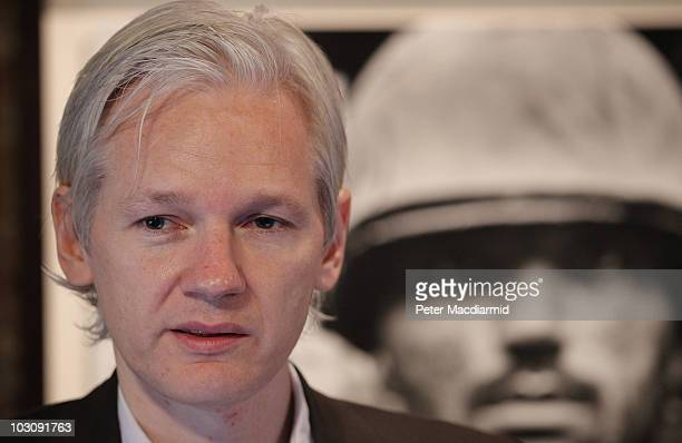 Julian Assange of the WikiLeaks website speaks to reporters in front of a Don McCullin Vietnam war photograph at The Front Line Club on July 26, 2010...