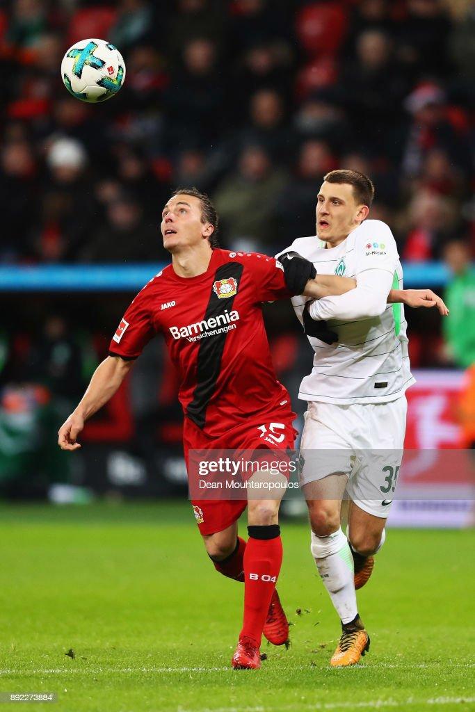 Julian Baumgartlinger of Bayer 04 Leverkusen battles for the ball with Maximilian Eggestein of Werder Bremen during the Bundesliga match between Bayer 04 Leverkusen and SV Werder Bremen at BayArena on December 13, 2017 in Leverkusen, Germany.