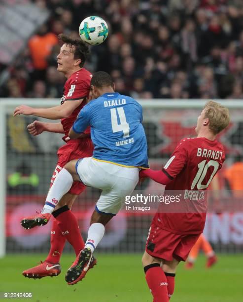 Julian Baumgartlinger of Leverkusen Abdou Diallo of Mainz and Julian Brandt of Leverkusen battle for the ball during the Bundesliga match between...