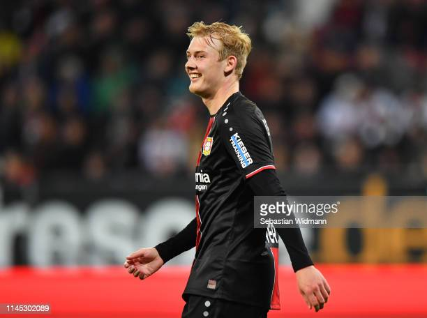 Julian Brandt of Bayer 04 Leverkusen smiles in celebration as he scores his team's fourth goal during the Bundesliga match between FC Augsburg and...
