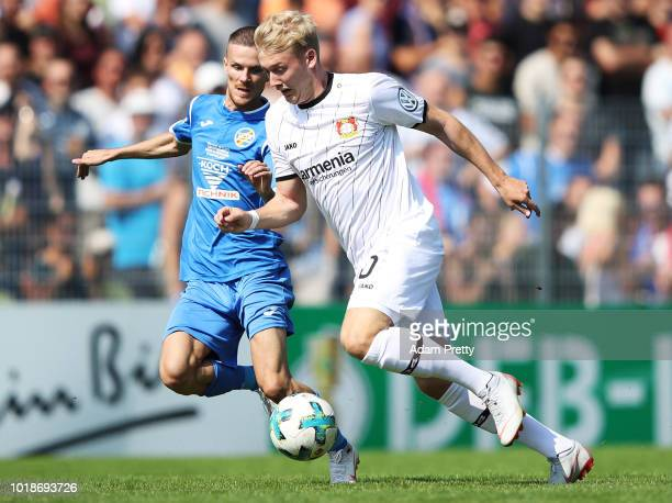 Julian Brandt of Bayer Leverkusen is tackled by Kreshnik Lushtaku of 1 CfR Pforzheim during the DFB Cup match between 1 CfR Pforzheim and Bayer...
