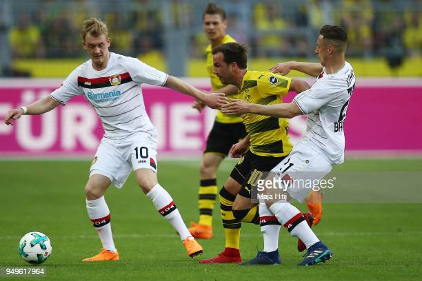 Julian Brandt of Bayer Leverkusen Mario Goetze of Dortmund and Dominik Kohr of Bayer Leverkusen fight for the ball during the Bundesliga match...
