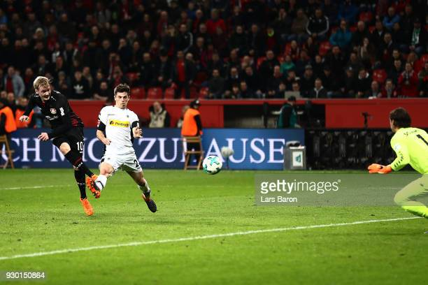 Julian Brandt of Bayer Leverkusen scores a goal past Jonas Hofmann of Moenchengladbach to make it 20 during the Bundesliga match between Bayer 04...