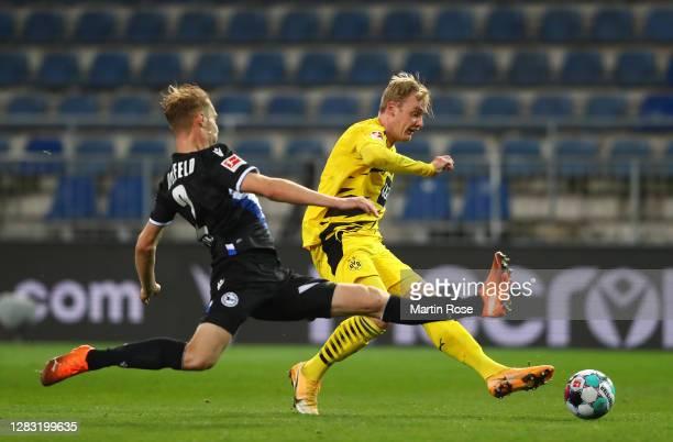 Julian Brandt of Borussia Dortmund shoots past Brian Behrendt of Arminia Bielefeld during the Bundesliga match between DSC Arminia Bielefeld and...