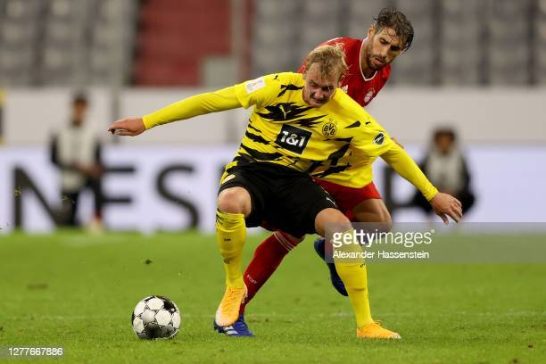 Julian Brandt of Dortmund runs with the ball with Javier Martinez of FC Bayern München during the Supercup 2020 match between FC Bayern München and...