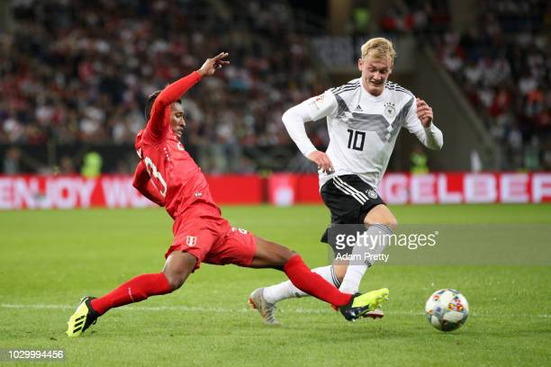 Julian Brandt of Germany is challanged by Pedro Aquino of Peru during the International Friendly match between Germany and Peru at RheinNeckarArena...