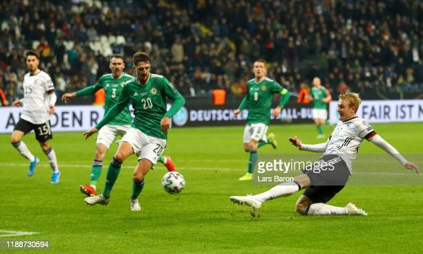 Julian Brandt of Germany scores his team's sixth goal as Craig Cathcart of Northern Ireland reacts during the UEFA Euro 2020 Qualifier between...