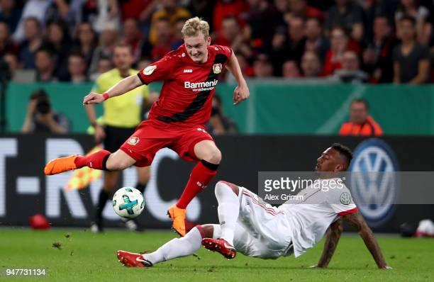 Julian Brandt of Lerverkusen and Jerome Boateng of Bayern battle for the ball during the DFB Cup semi final match between Bayer 04 Leverkusen and...