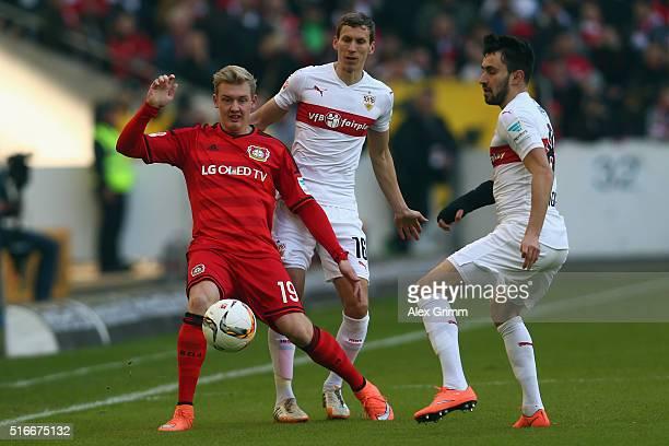 Julian Brandt of Leverkusen is challenged by Florian Klein and Lukas Rupp of Stuttgart during the Bundesliga match between VfB Stuttgart and Bayer...