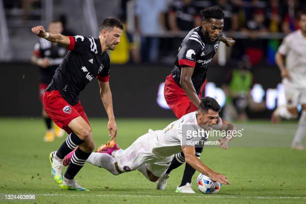 Julian Carranza of Inter Miami is tripped up while battling for the ball against Brendan Hines-Ike and Donovan Pines of D.C. United during the first...