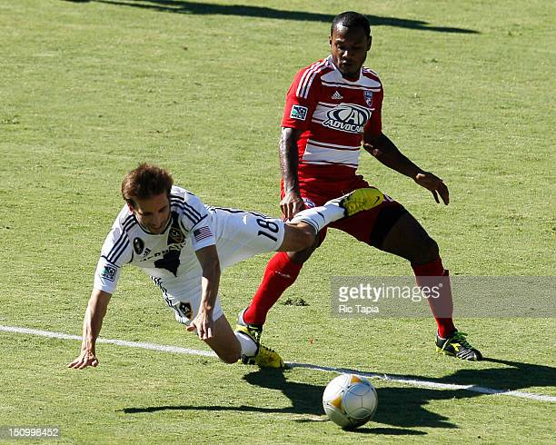 Julian de Guzman of FC Dallas trips Mike Magee of Los Angeles Galaxy as they battle for the ball during the MLS match at The Home Depot Center on...