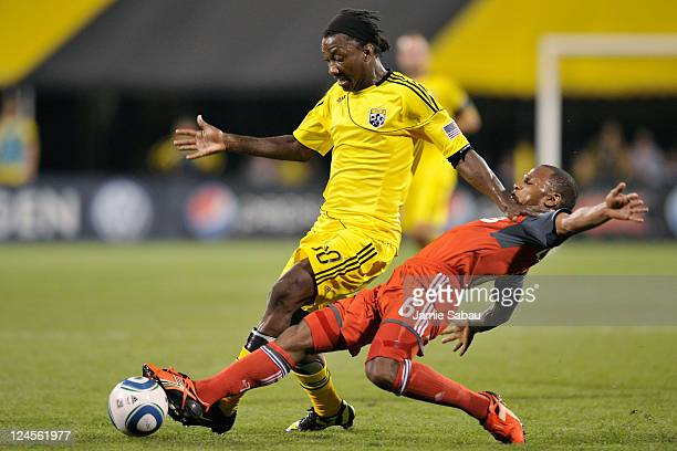 Julian de Guzman of Toronto FC slides in to kick the ball away from Andres Mendoza of the Columbus Crew on September 10 2011 at Crew Stadium in...