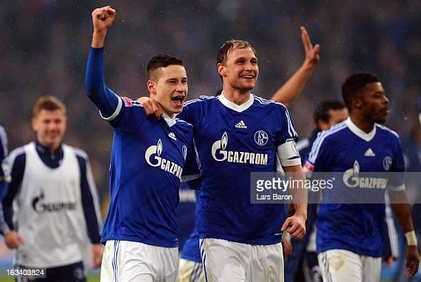 Julian Draxler and Benedikt Hoewedes celebrate after winning the Bundesliga match between FC Schalke 04 and Borussia Dortmund at VeltinsArena on...