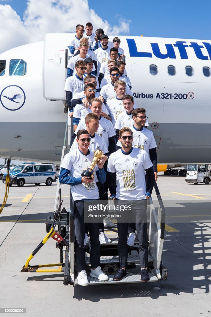 Julian Draxler (front row, L) and his team mates present the trophy as they depart the plane carrying the Germany National Football Team during the arrival at Frankfurt International Airport on July 3, 2017 in Frankfurt am Main, Germany.