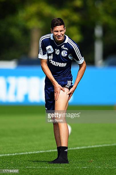 Julian Draxler holds his injured leg during a FC Schalke 04 training session on August 22 2013 in Gelsenkirchen Germany