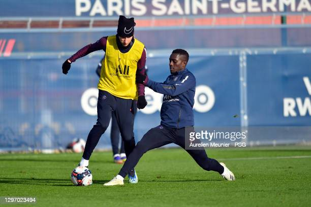 Julian Draxler is tackled by teammate Idrissa Gueye during a Paris Saint-Germain training session at Ooredoo Center on January 18, 2021 in Paris,...