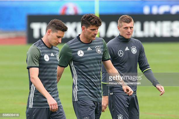 Julian Draxler Mario Gomez and Toni Kroos of Germany look on during a Germany training session ahead of the UEFA EURO 2016 at Ermitage Evian on June...