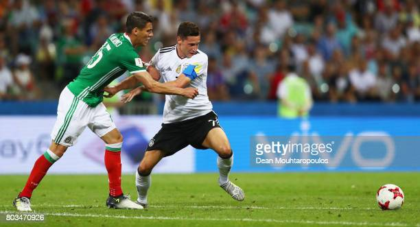 Julian Draxler of Germany and Hector Moreno of Mexico compete for the ball during the FIFA Confederations Cup Russia 2017 SemiFinal between Germany...