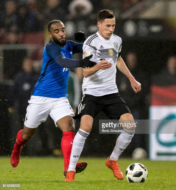 Julian Draxler of Germany is challenged by Alexandre Lacazette of France during the International friendly match between Germany and France at...