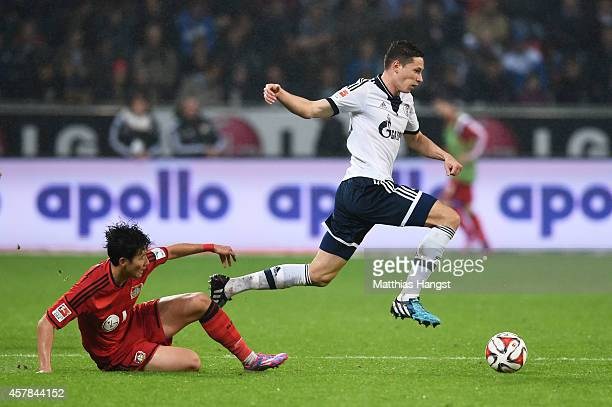 Julian Draxler of Schalke goes past the challenge from Son HeungMin of Bayer Leverkusen during the Bundesliga match between Bayer 04 Leverkusen and...