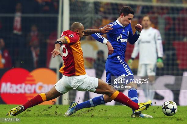 Julian Draxler of Schalke is challenged by Felipe Melo of Galatasaray during the UEFA Champions League Round of 16 first leg match between...